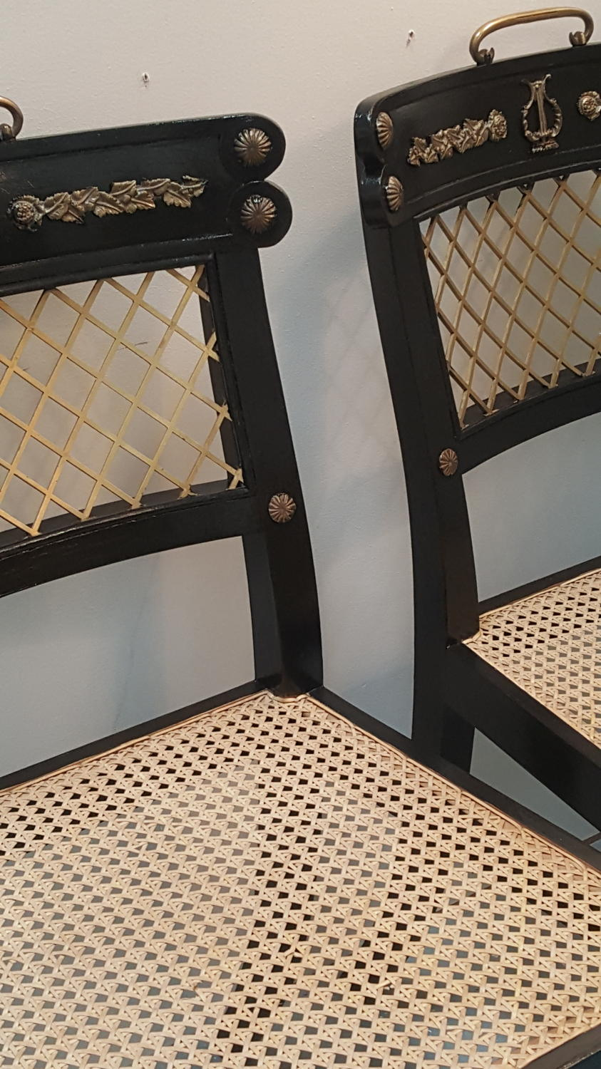 Pair of Regency style hall chairs with brass trellis backs and caned s